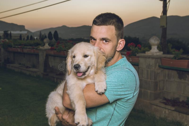 Guy with his kissing his puppy dog stock photo