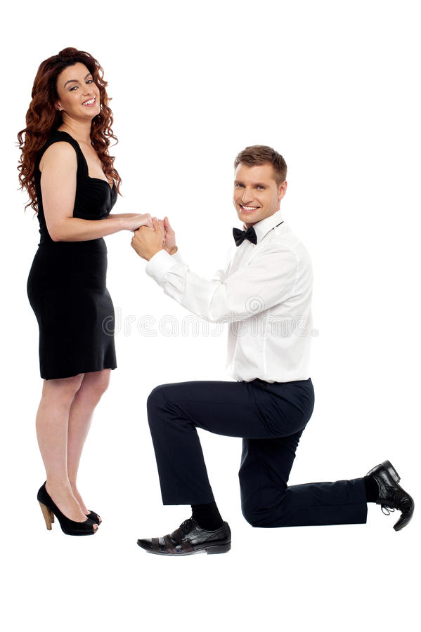 Guy on his knees proposing girl to marry. Handsome guy on his knees proposing girl to marry him holding hands of his beloved royalty free stock photo
