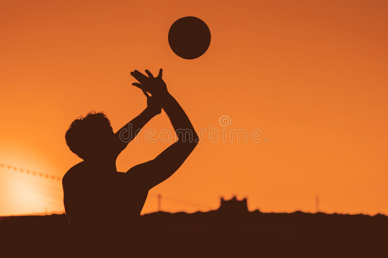 Guy hitting volleyball in shadow style image. royalty free stock images