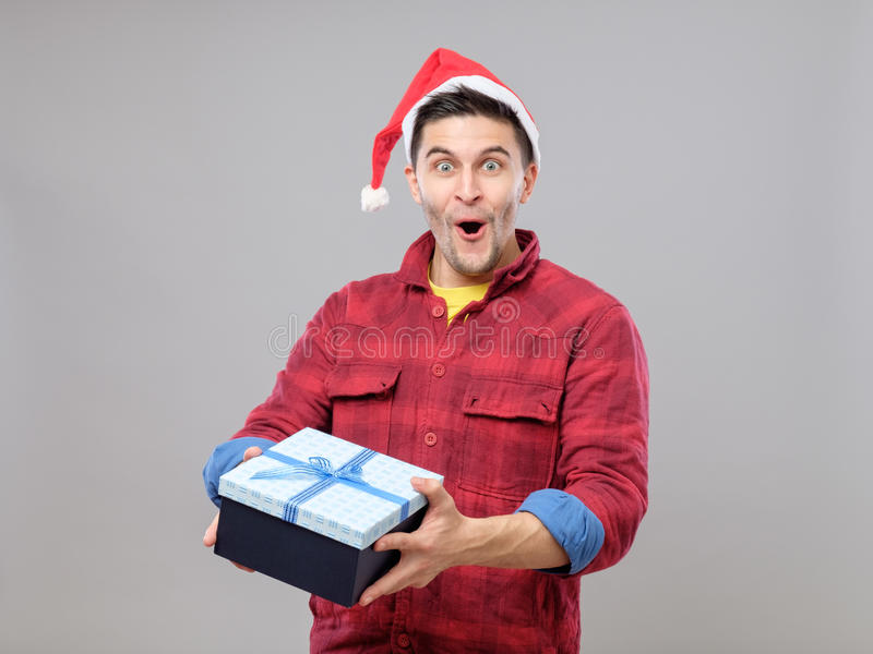 Guy holding a christmas gift. Handsome guy holding a gift and emotionally happy Christmas on gray background stock photo