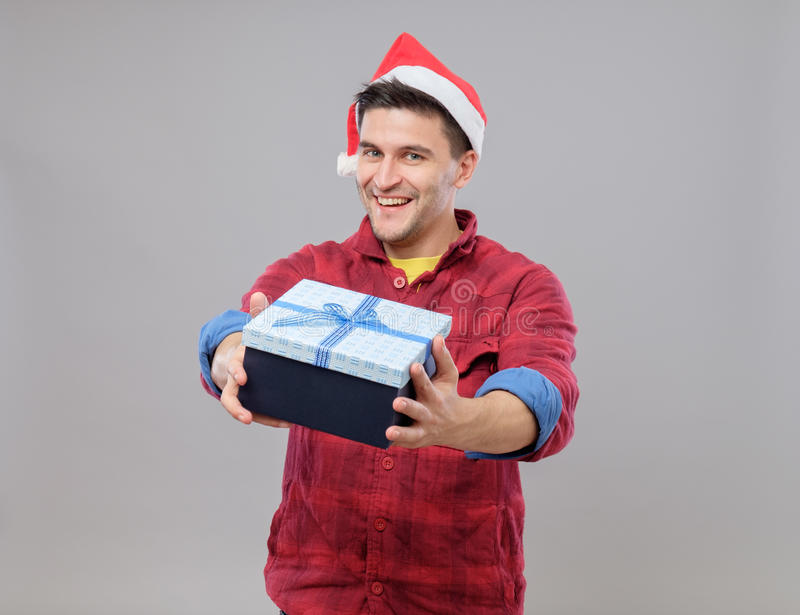 Guy holding a christmas gift. Handsome guy holding a gift and emotionally happy Christmas isolated on gray background stock image