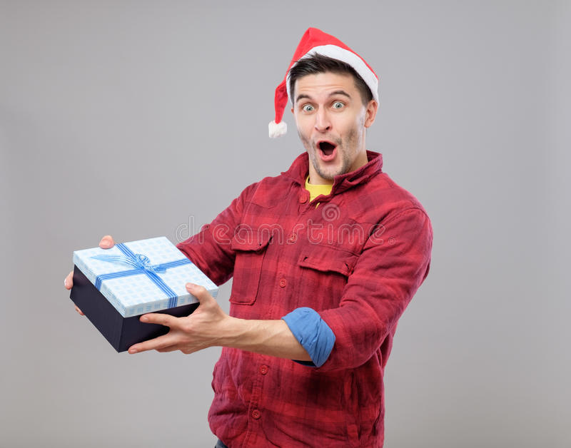 Guy holding a christmas gift. Handsome guy holding a gift and emotionally happy Christmas isolated on gray background royalty free stock photos