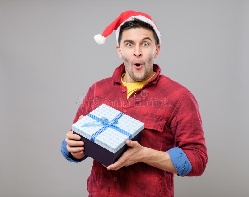 Guy holding a christmas gift. Handsome guy holding a gift and emotionally happy Christmas isolated on gray background royalty free stock images