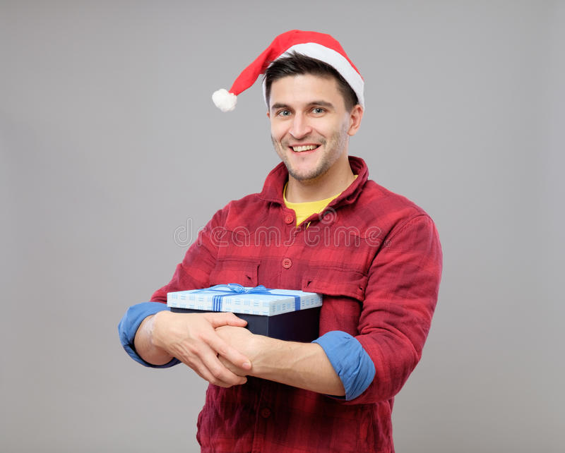 Guy holding a christmas gift. Handsome guy holding a gift and emotionally happy Christmas isolated on gray background stock photo