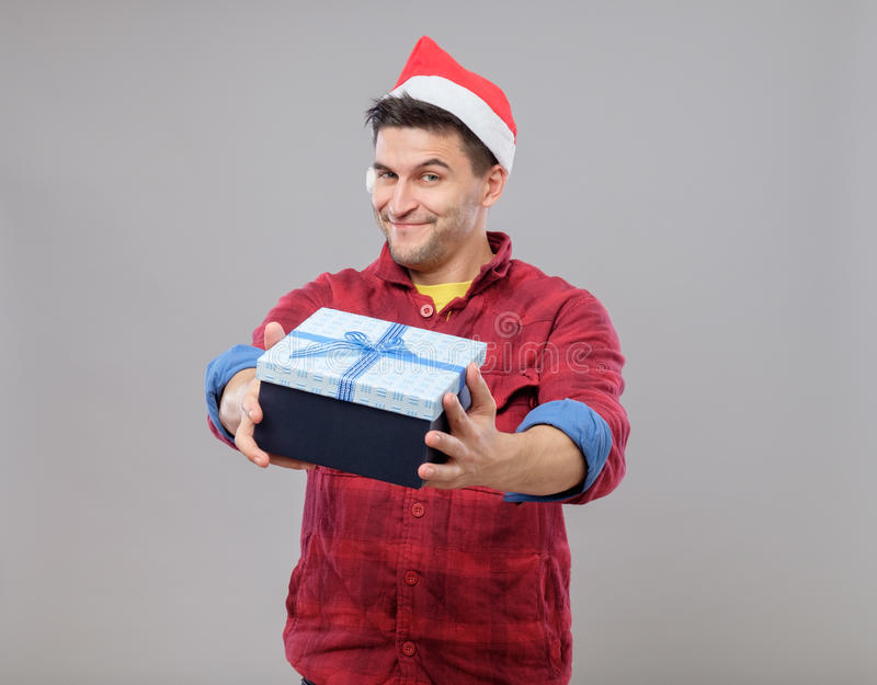 Guy holding a christmas gift. Handsome guy holding a gift and emotionally happy Christmas isolated on gray background royalty free stock image