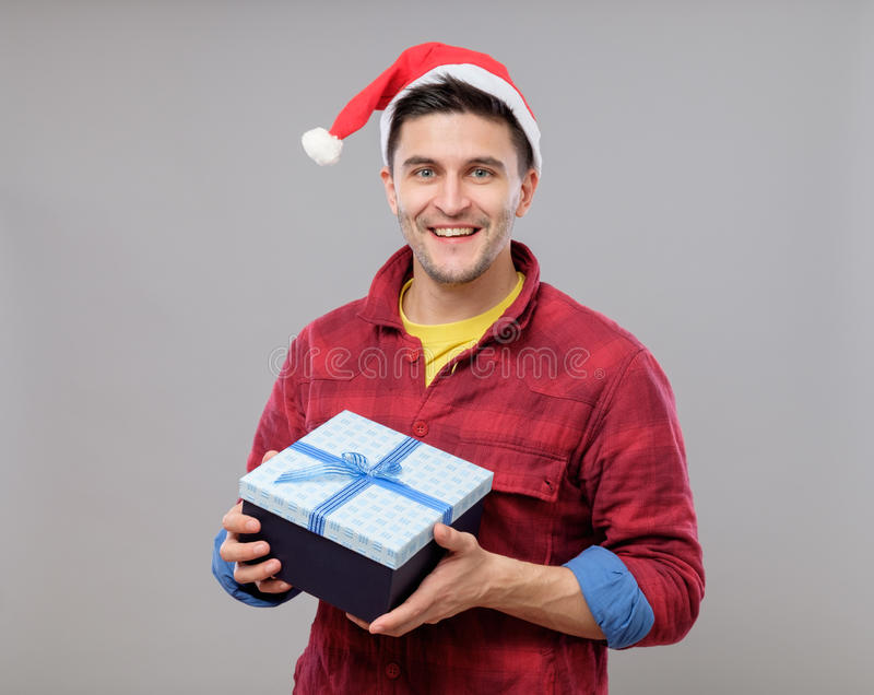 Guy holding a christmas gift. Handsome guy holding a gift and emotionally happy Christmas isolated on gray background royalty free stock photo