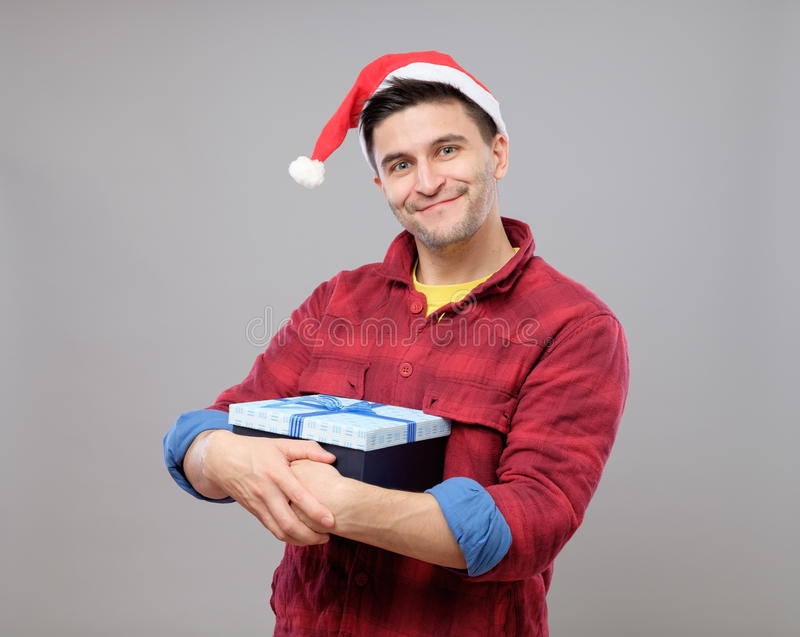 Guy holding a christmas gift. Handsome guy holding a gift and emotionally happy Christmas isolated on gray background stock photography