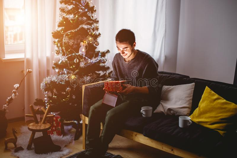 Guy holding a gift and emotionally happy Christmas.  stock image