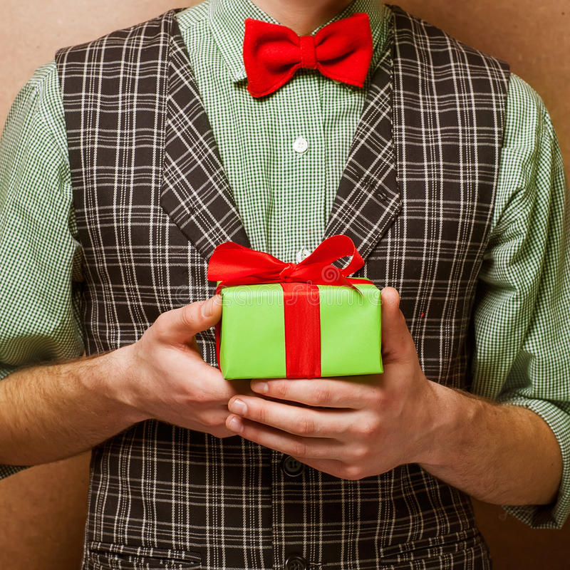 Guy holding a gift. In a suit and bow tie in a cage royalty free stock images