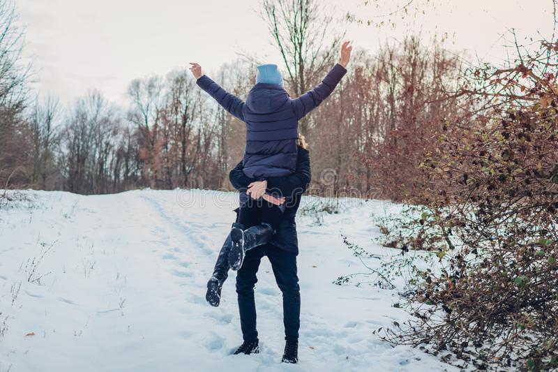 Guy holding and lifting his girlfriend in hands in winter forest. Girl raising arms. People having fun outdoors royalty free stock photography