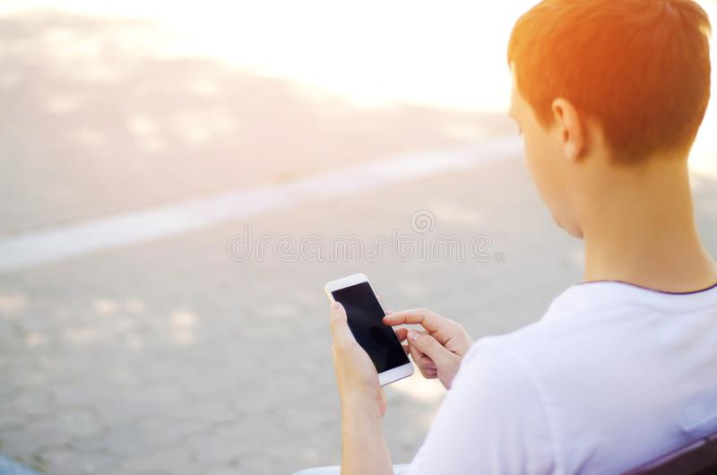 The guy is holding a mobile smartphone and looking at the screen. telephone dependence, social networks. work on the Internet. wri. Te message. sunny day. close stock photo