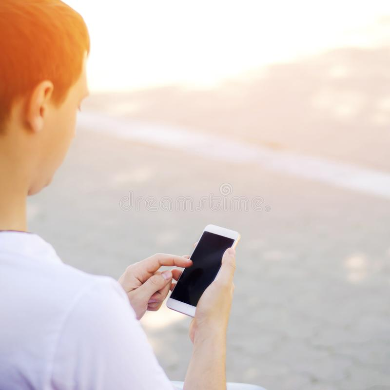 The guy is holding a mobile smartphone and looking at the screen. telephone dependence, social networks. work on the Internet. Write message. sunny day. close stock photography