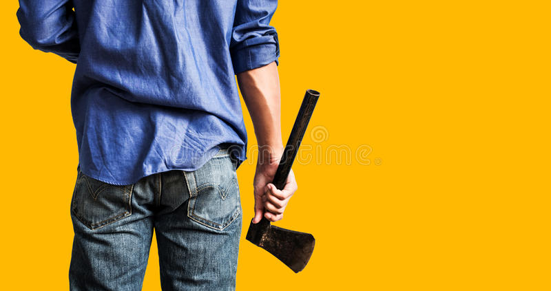 A guy holding old rusty axe, close up rear view, on yellow background with copy space stock photos