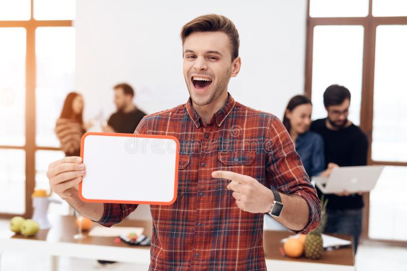 The guy is holding a white board. He is in the office where there are other employees stock photo