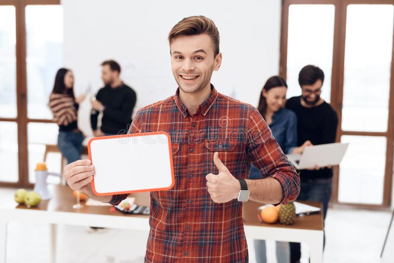 The guy is holding a white board. He is in the office where there are other employees stock photos