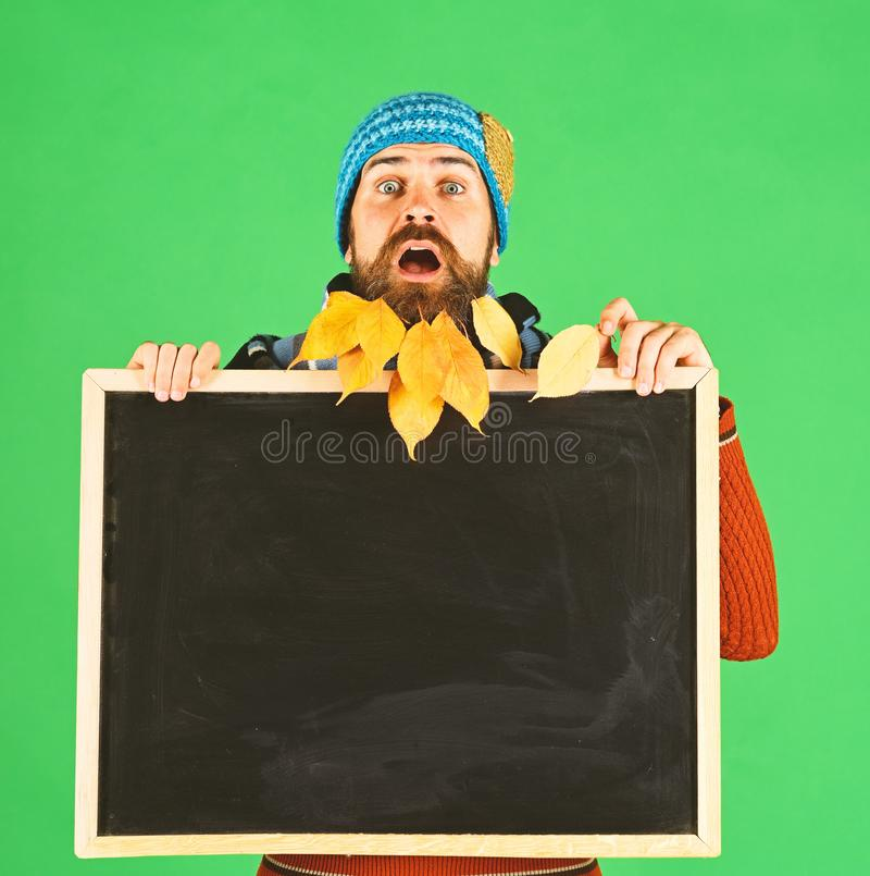 Guy holds chalkboard at barbershop, copy space. Man in hat. Guy holds chalkboard at barbershop, copy space. Man in warm hat holds blackboard and leaf on green royalty free stock image