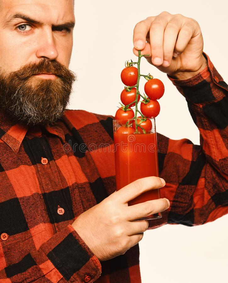Guy with homegrown harvest. Farmer with strict face shows tomatoes. Guy with homegrown harvest. Farmer with strict face shows bunch of red cherry tomatoes. Farm stock images