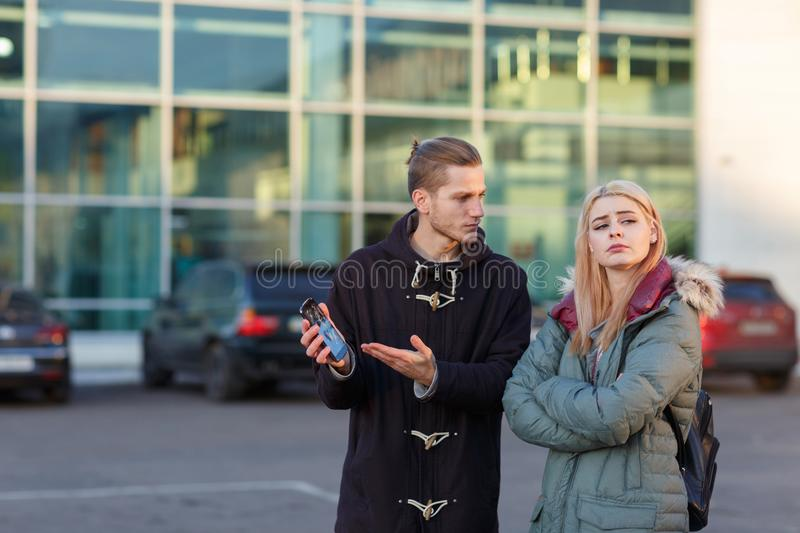 Guy is indignant at the girl because of the broken smartphone, the girl turned her face offendedly. A young European couple swearing in the street, the guy is stock photography