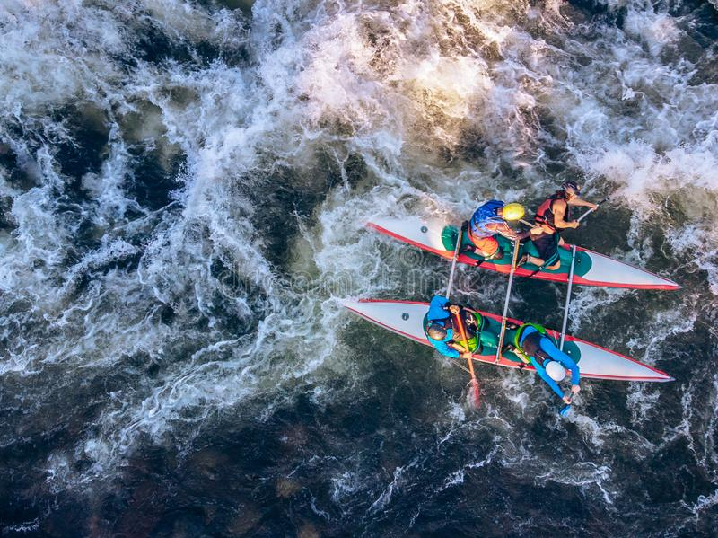 Guy in kayak sails mountain river. Whitewater kayaking, extreme sport rafting. Aerial top view royalty free stock images