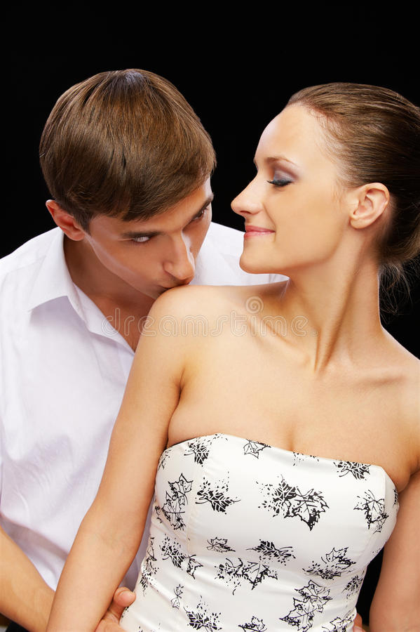 Guy kissing girls shoulder. Portrait of young romantic couple on black. man kissing woman's shoulder and she is closing her eyes royalty free stock photo