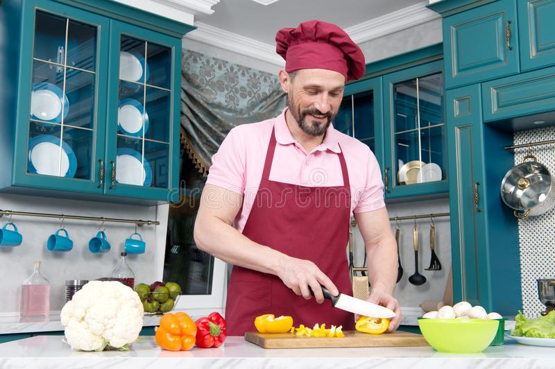 Guy with knife cutting orange pepper on table. Cook dressed in apron prepare dinner with paprika. Man in hat preparing vegetables. royalty free stock images