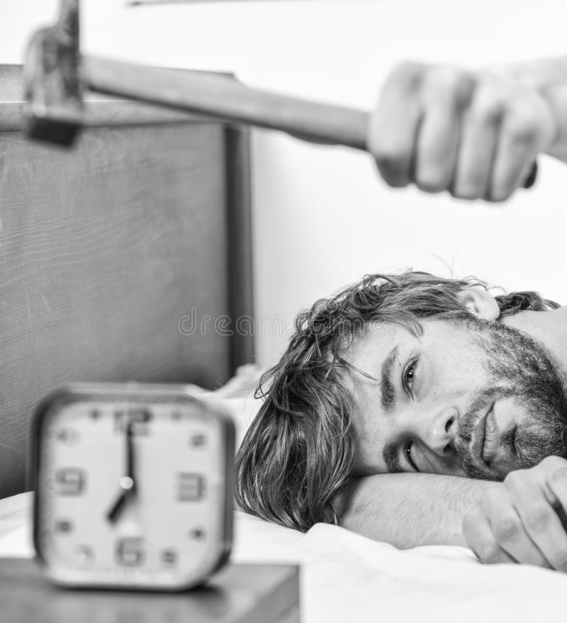 Guy knocking with hammer alarm clock ringing. Break discipline regime. Annoying sound. Man bearded annoyed sleepy face. Lay pillow near alarm clock. Stop royalty free stock photos