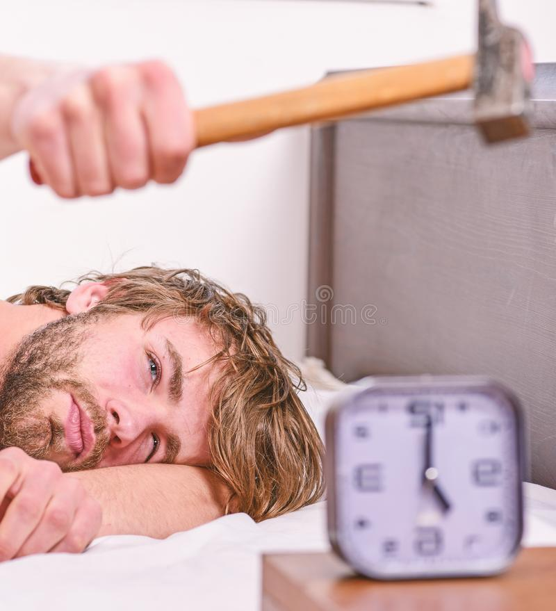 Guy knocking with hammer alarm clock ringing. Break discipline regime. Annoying sound. Man bearded annoyed sleepy face. Lay pillow near alarm clock. Stop royalty free stock photo