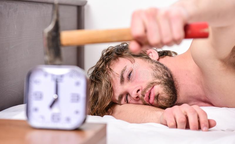 Guy knocking with hammer alarm clock ringing. Break discipline regime. Annoying sound. Stop ringing. Annoying ringing. Alarm clock. Man bearded annoyed sleepy royalty free stock photography