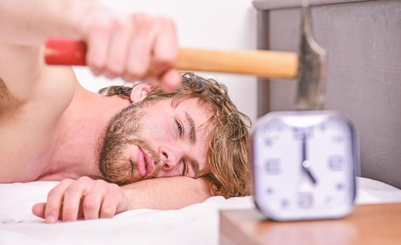 Guy knocking with hammer alarm clock ringing. Break discipline regime. Annoying sound. Stop ringing. Annoying ringing. Alarm clock. Man bearded annoyed sleepy stock photo