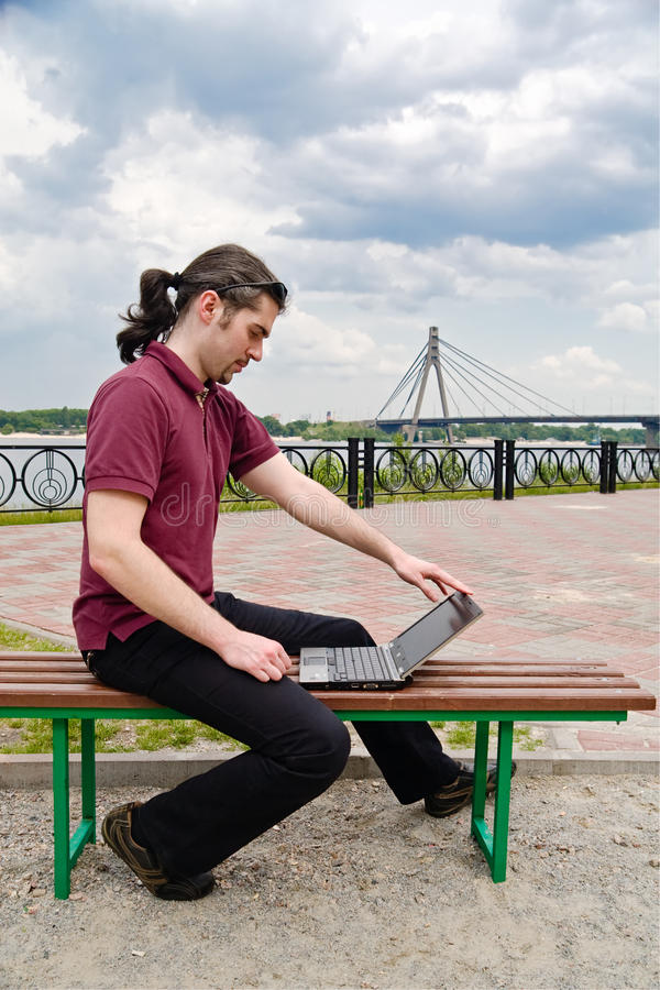 Guy with laptop in the park stock image