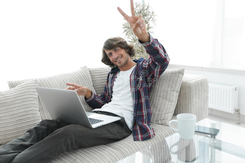 Happy guy with laptop sitting on sofa and showing his hand a winning gesture. Guy with laptop sitting on sofa and showing hand winning triumph. concept of a royalty free stock photography