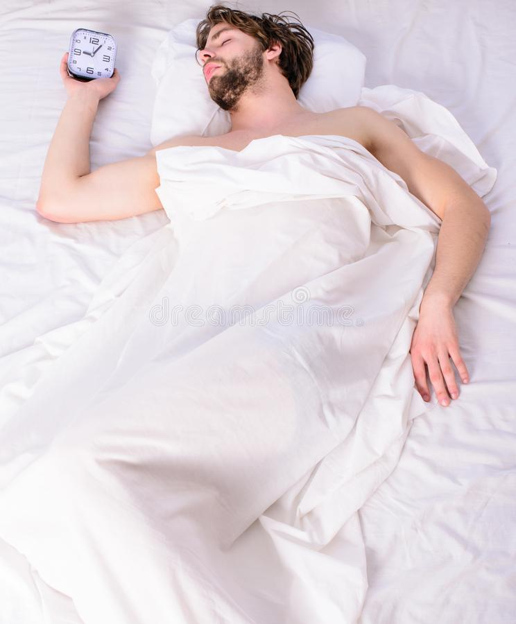 Guy lay under white bedclothes. Fresh bedclothes concept. Man sleepy drowsy unshaven bearded face covered with blanket. Having rest. Turn off alarm clock. Man royalty free stock photos