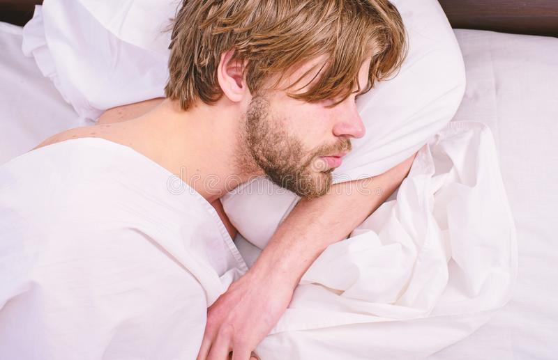 Guy lay under white bedclothes. Man unshaven handsome relaxing bed. Power napping may help you get through day. Have nap. Relax. Man sleepy drowsy unshaven stock photography