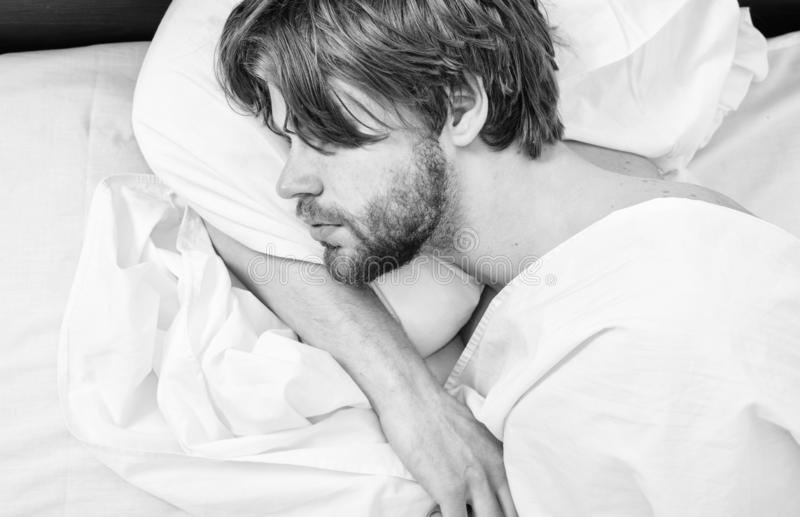 Guy lay under white bedclothes. Man unshaven handsome relaxing bed. Power napping may help you get through day. Have nap. Relax. Man sleepy drowsy unshaven royalty free stock image