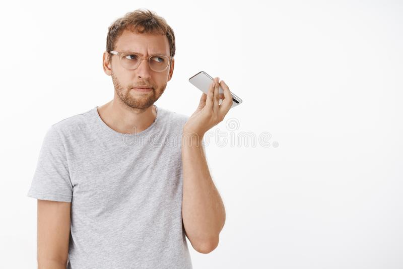 Guy listening audio message cannot understand what strange noise coming from dynamics holding smartphone near ear stock photography