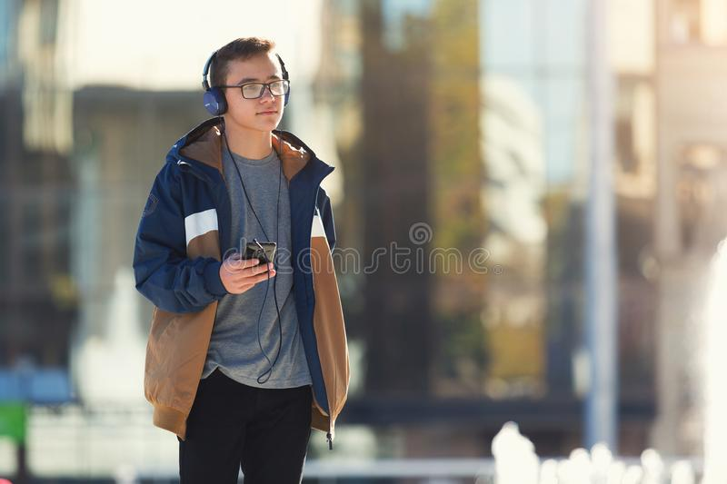 Guy listening to music and using phone outdoors. Copy space stock photography