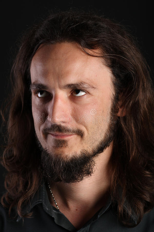 Guy With Long Hair And Goatee Looking Up On Black Royalty Free Stock Photography