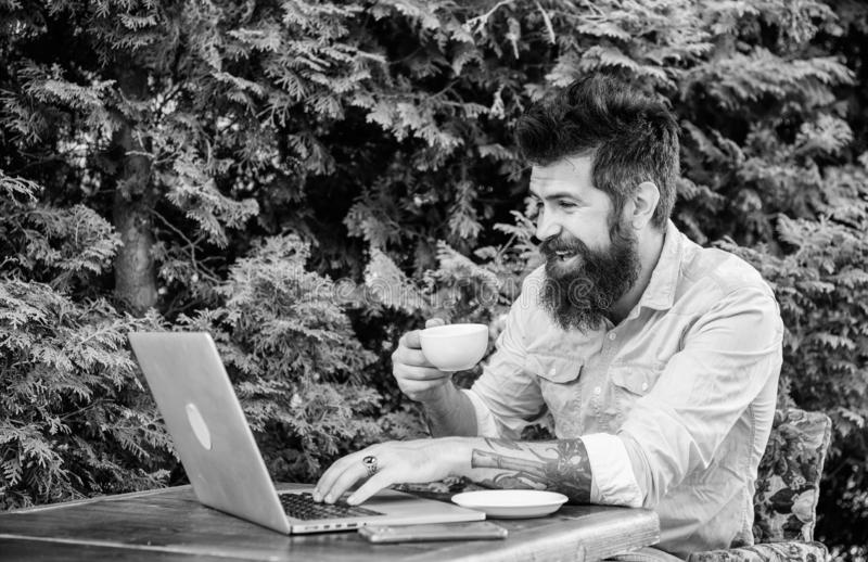 Guy looking for apartment. Find apartment for holidays or vacation. Planning vacation. Man bearded hipster sit outdoors. With laptop surfing internet and royalty free stock images
