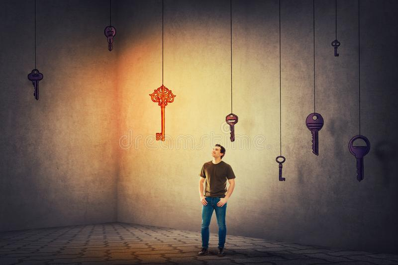Guy looking up finding the magic key to success. Confident young man standing in a dark room looking up finding the magic key to success. Concept of business stock image