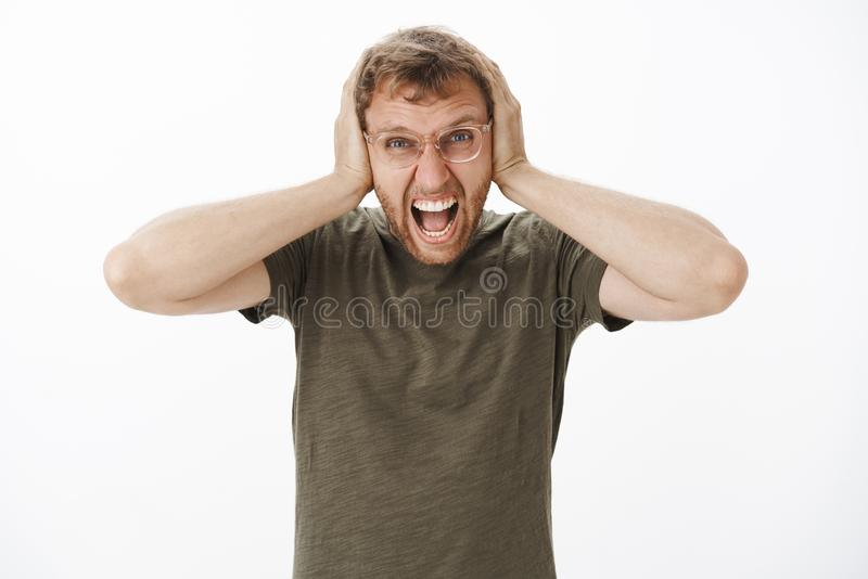 Guy lose temper being with loud noises at night yelling out loud with angry outrage expression covering ears with. Palms on head being in rage over white stock photos
