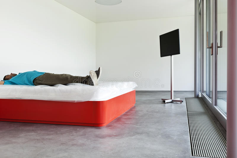 Download Guy lying on the bed stock image. Image of floor, modern - 26099201