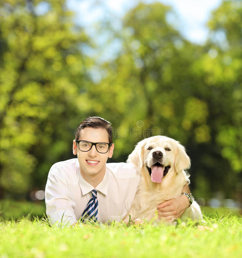 Guy lying on a green grass and hugging his dog in a park. Guy lying on a green grass and hugging his labrador retriever dog in a park, shot with a tilt and shift royalty free stock photos