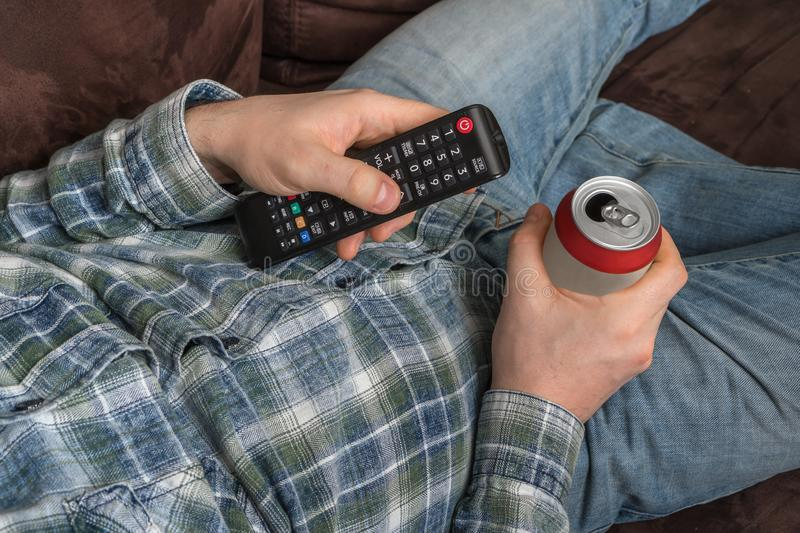 Guy is lying on sofa with TV remote control and drinking beer royalty free stock photo