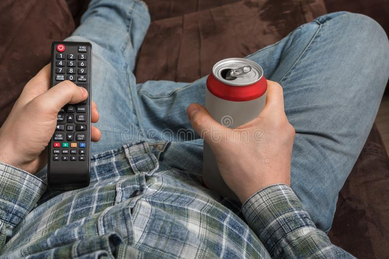 Guy is lying on sofa with TV remote control and drinking beer stock photography