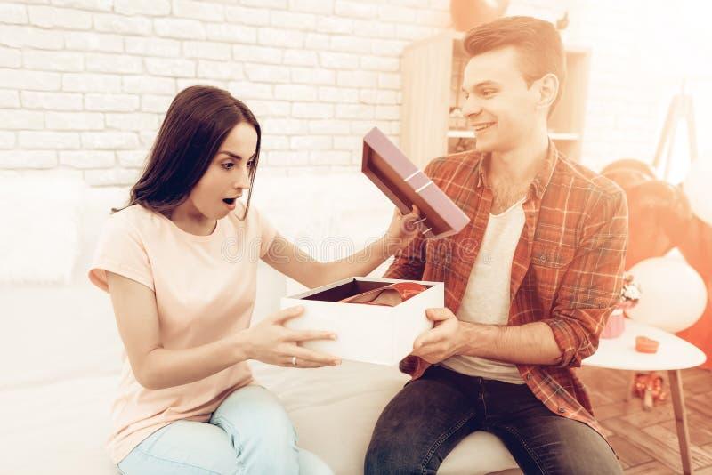 Guy Makes ein Geschenk zur Freundin an Valentinsgruß ` s Tag lizenzfreie stockfotografie