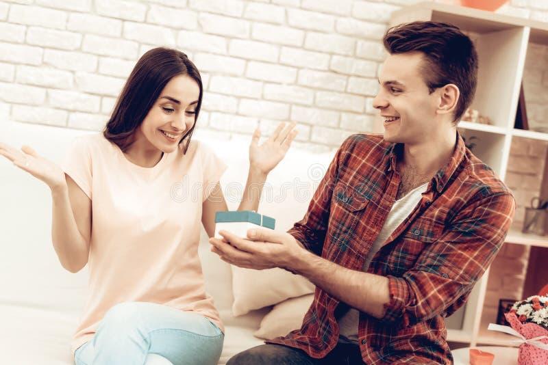 Guy Makes en gåva till flickvännen på dag för valentin` s arkivbilder