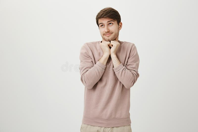 Guy makes finger framing to model pose. Portrait of happy emotive handsome male photographer making frame gesture and. Looking through it, trying to find good royalty free stock image