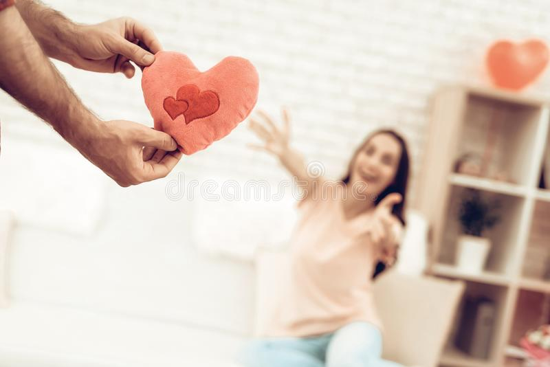 Guy Makes A Gift To Girlfriend On Valentine`s Day. Love Each Other. Sweetheart`s Romantic Holiday Concept. Young And Handsome. Happy Relationship. Pillow Heart royalty free stock image