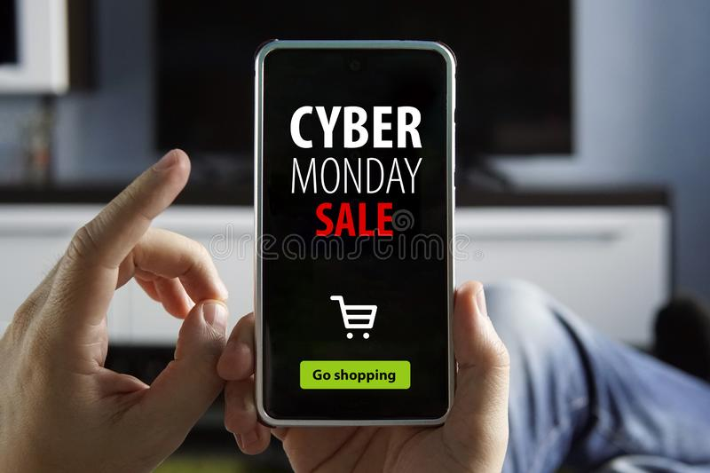 Guy makes purchases through mobile app without leaving home. Convenient service. Hand Holding Mobile with the text: Cyber Monday. Hand Holding Mobile with the royalty free stock images