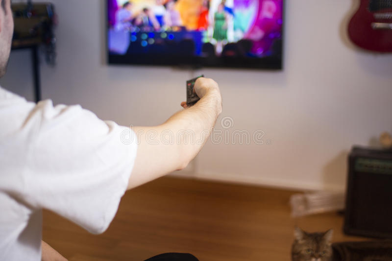 Guy, man, hipster switch channels on the TV, in room design with a guitar, no signal stock images